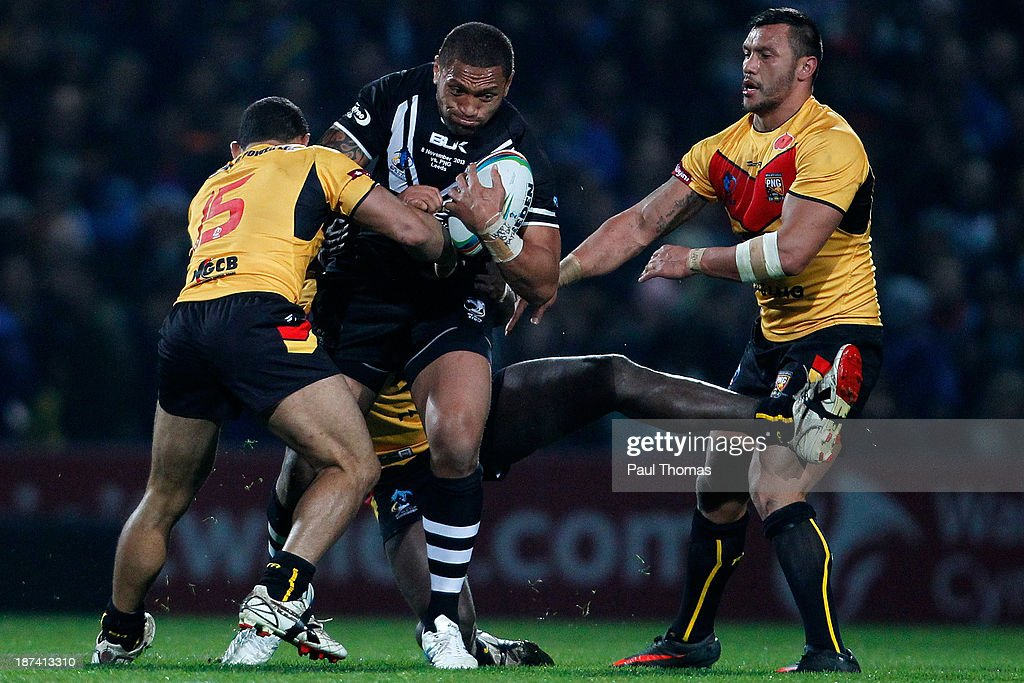 Manu Vatuvei of New Zealand is tackled by Paul Aiton (L) and Joe Bruno of Papua New Guinea during the Rugby League World Cup Group B match at Headingley Stadium on November 8, 2013 in Leeds, England.