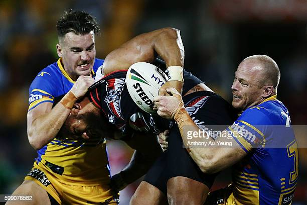 Manu Vatuvei of the Warriors is tackled by Clinton Gutherson and Beau Scott of the Eels during the round 26 NRL match between the New Zealand...