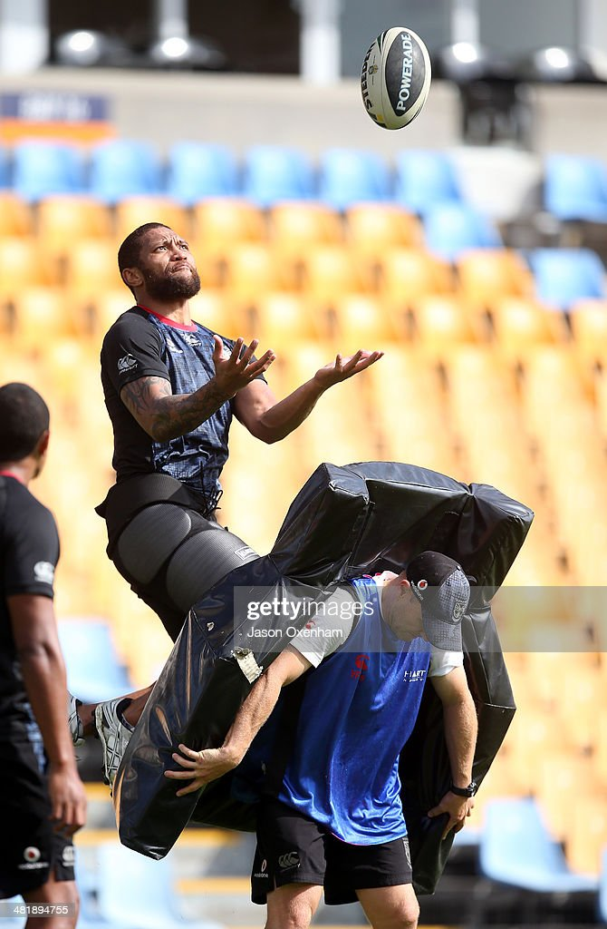 Manu Vatuvei of the Warriors takes a high ball with Warriors assistant coach Andrew McFadden bracing the pads during a New Zealand Warriors NRL training session at Mt Smart Stadium on April 2, 2014 in Auckland, New Zealand.