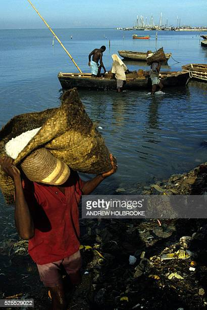 Manual laborers unload heavy sacks of salt from a small boat at Port au Prince