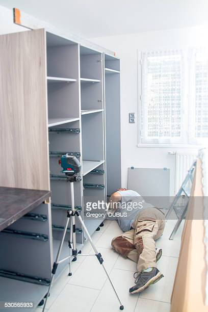 Manual worker adjusts new furniture kitchen