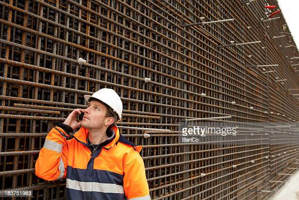 Manual worker busy with road construction and calling his boss.