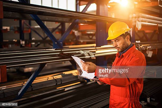 Manual worker going through paperwork in aluminum mill.