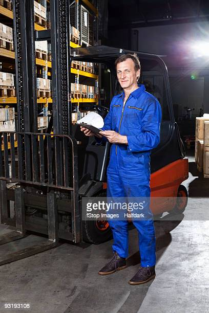 A manual worker holding a checklist in a metal parts warehouse