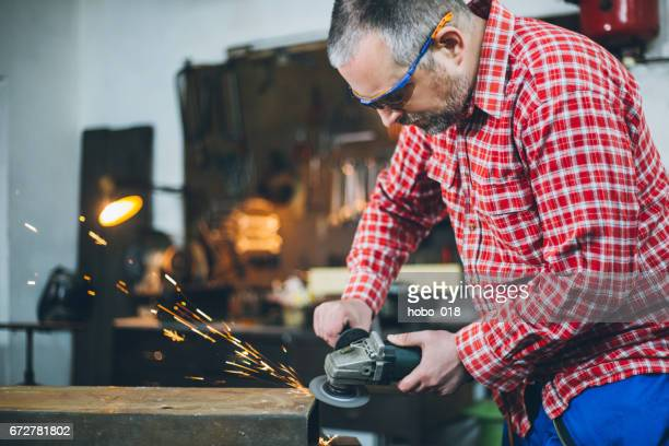Manual worker in a workshop using grinder