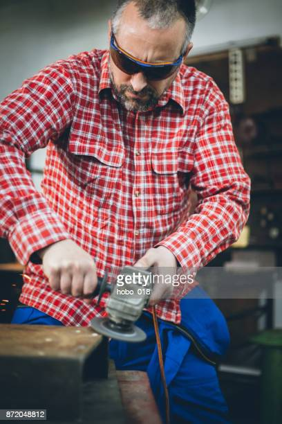 Manual worker in a workshop using grinder