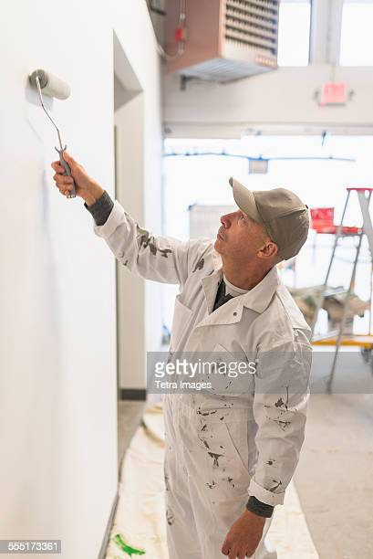 Manual worker painting wall