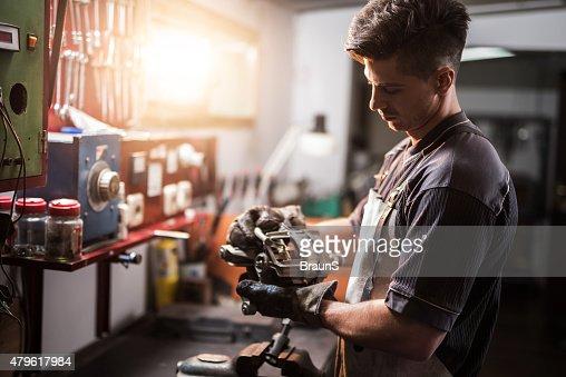 Manual worker repairing electric motor in a workshop.