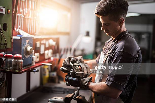 Manual worker repairing electric motor in a workshop.