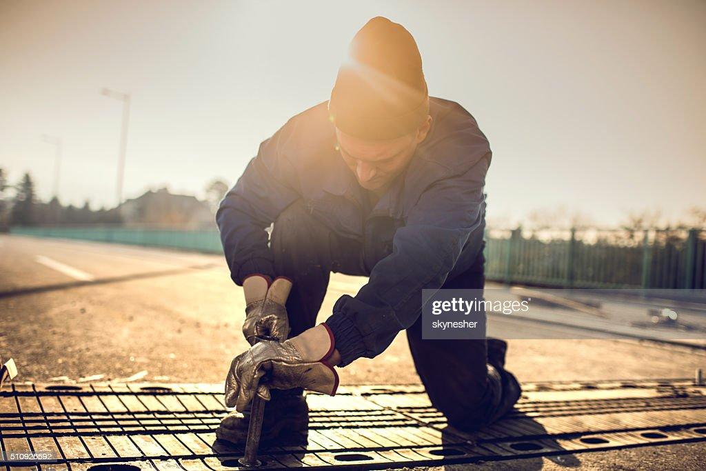 Manual worker repairing road on a bridge at sunset.
