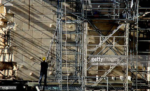 Manual Worker Standing On Scaffolding Of Building