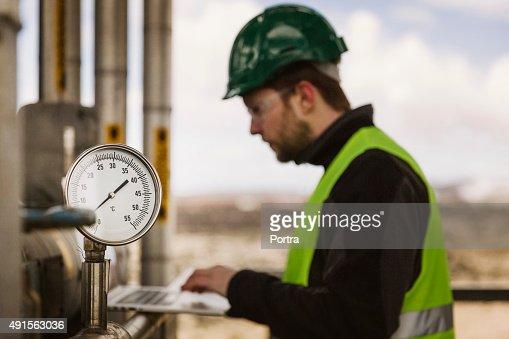 Manual worker using laptop by industrial gauge