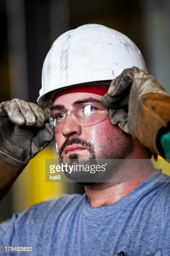 Manual worker wearing hardhat and safety glasses