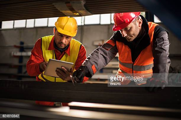Manual workers cooperating while measuring metal in aluminum mill.
