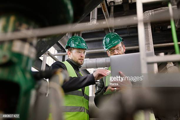 Manual workers discussing while using laptop at factory