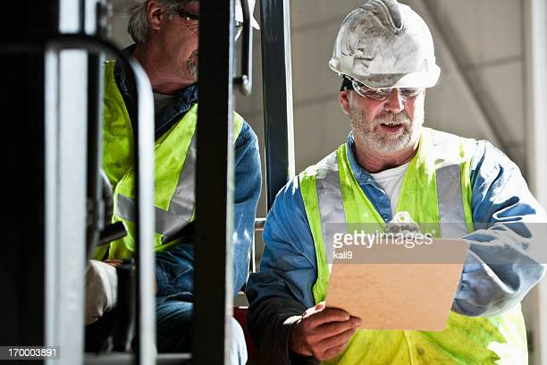 Manual workers reading clipboard