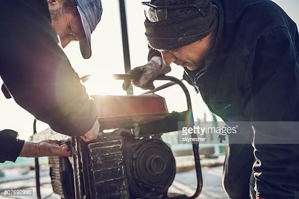 Manual workers repairing power generator.