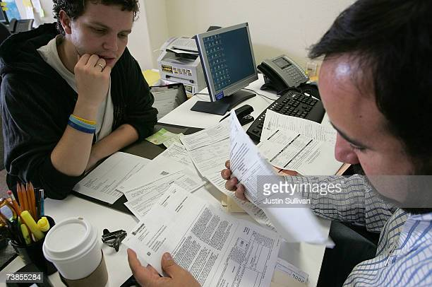 Manuel Alvarez helps Ricardo Guido with his taxes at Latino Taxes April 10 2007 in Oakland California US taxpayers are rushing to meet the Tuesday...