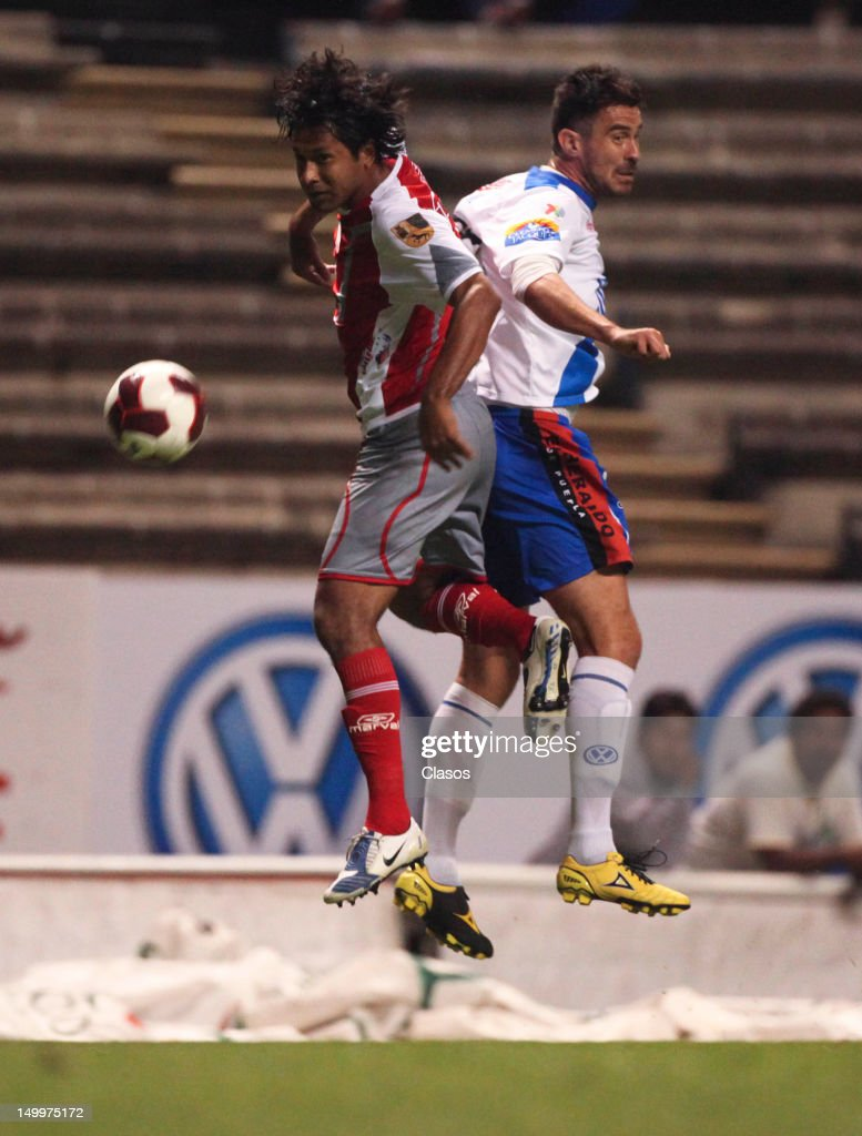 Manuel de la Torre of Lobos (L) struggles for the ball with Matias Abelairas of Puebla (R) during a match between Puebla and Lobos BUAP as part of the Copa MX 2012 at Cuauhtemoc Stadium on August 07, 2012 in Puebla, Mexico.