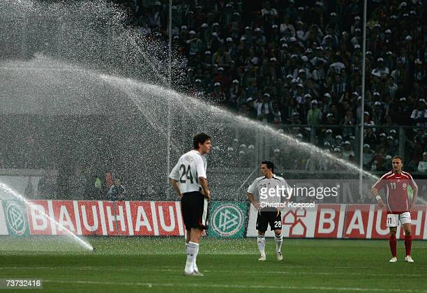 Manuel Friedrich and Piotr Trochowski of Germany watch the water fountain starts during the international friendly match between Germany and Denmark...
