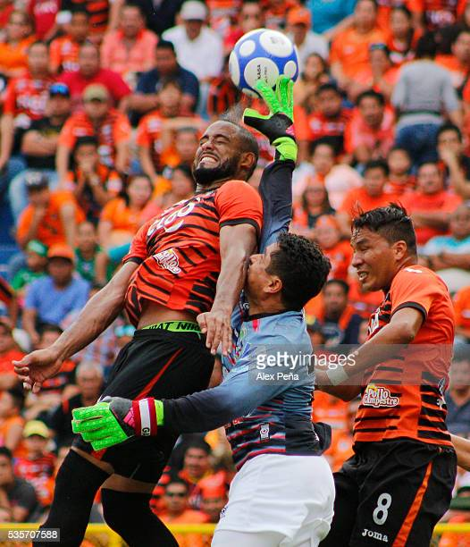 Manuel Gonzalez goalkeeper of Dragon jumps for the ball with Hector Ramos and Santos Ortiz of Aguila during the Final match between Aguila and CD...