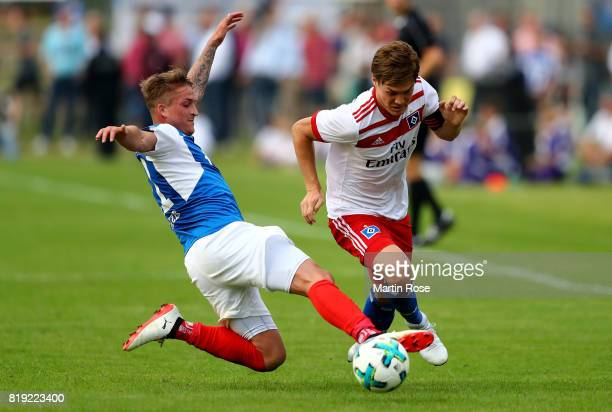 Manuel Janzer of Kiel and Gotoku Sakai of Hamburg battle for the ball during the preseason friendly match between Holstein Kiel and Hamburger SV at...