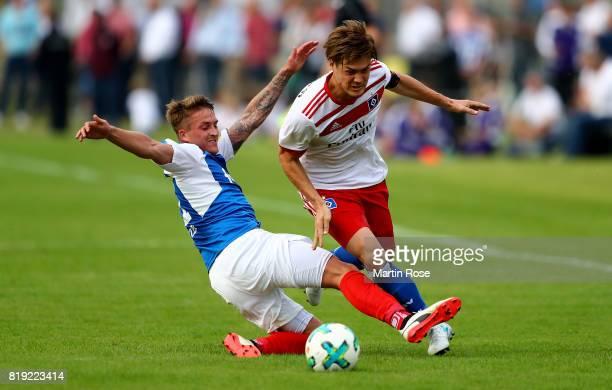 Manuel Janzer of Kiel and Gotoku Sakai of Hamburg battle for the ball during the preseason friendly match between Holstein Kiel and Hamburger SV at...