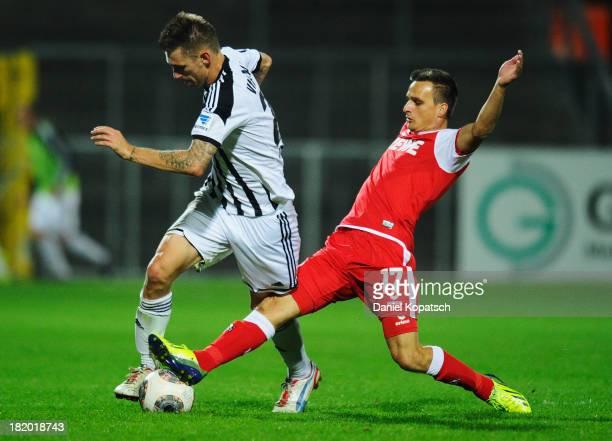 Manuel Junglas of Aalen is challenged by Slawomir Peszko of Koeln during the second Bundesliga match between VfR Aalen and 1 FC Koeln at ScholzArena...