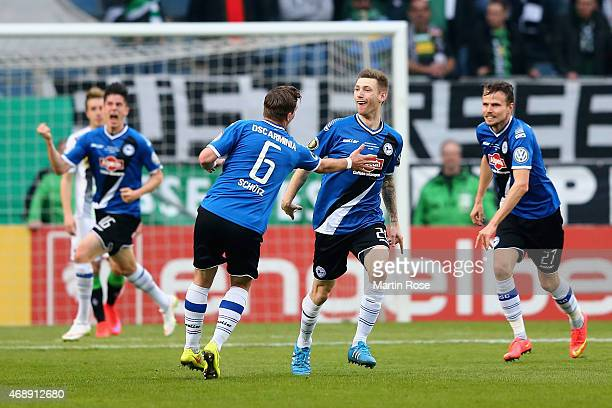 Manuel Junglas of Arminia Bielefeld celebrates with team mates as he scores the opening goal during the DFB Cup Quarter Final match between Arminia...