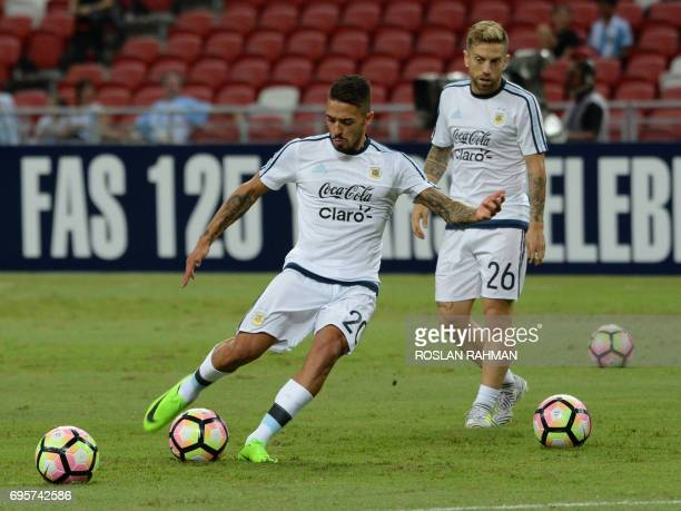 Manuel Lanzini and Alejandro Gómez of Argentina warm up before the start of their international friendly football match against Singapore at the...