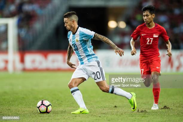 Manuel Lanzini of Argentina dribbles Nazrul Nazari of Singapore during the International Test match between Argentina and Singapore at National...