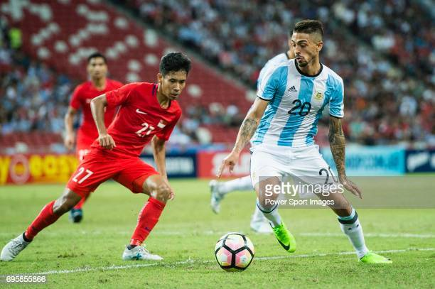 Manuel Lanzini of Argentina fights for the ball with Nazrul Nazari of Singapore in action during the International Test match between Argentina and...