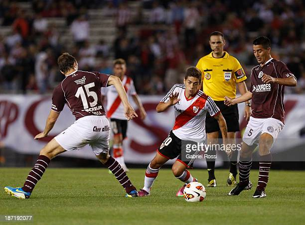 Manuel Lanzini of River Plate fights for the ball with Leandro Somoza of Lanus during a match between River Plate and Lanus as part of Copa Total...