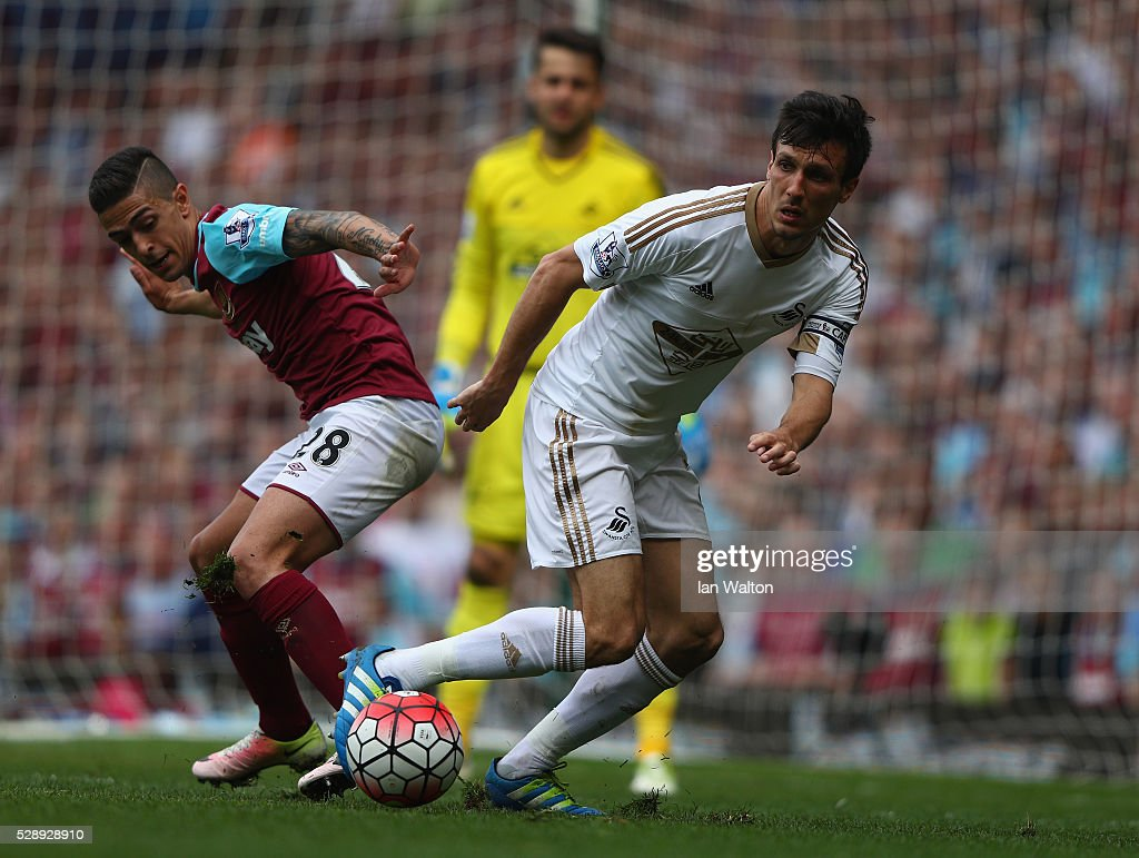 <a gi-track='captionPersonalityLinkClicked' href=/galleries/search?phrase=Manuel+Lanzini&family=editorial&specificpeople=7150862 ng-click='$event.stopPropagation()'>Manuel Lanzini</a> of West Ham tries to tackle <a gi-track='captionPersonalityLinkClicked' href=/galleries/search?phrase=Jack+Cork+-+Soccer+Player&family=editorial&specificpeople=4206991 ng-click='$event.stopPropagation()'>Jack Cork</a> of Swansea City during the Barclays Premier League match between West Ham United and Swansea City at the Boleyn Ground, May 7, 2016, London, England.