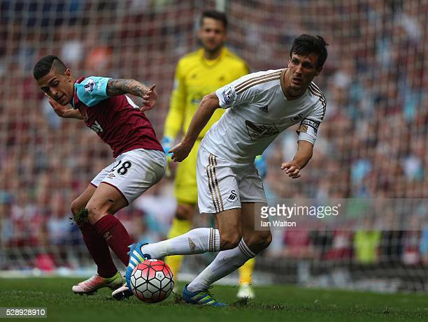 Manuel Lanzini of West Ham tries to tackle Jack Cork of Swansea City during the Barclays Premier League match between West Ham United and Swansea...