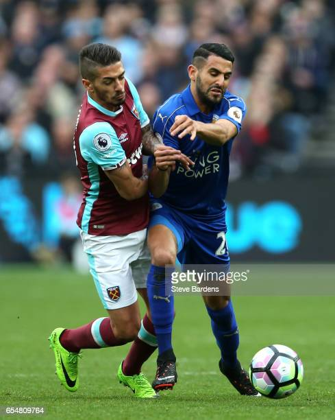 Manuel Lanzini of West Ham United and Riyad Mahrez of Leicester City battle for possession during the Premier League match between West Ham United...
