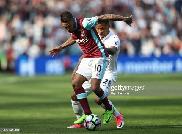 Manuel Lanzini of West Ham United is put under pressure from Luciano Narsingh of Swansea City during the Premier League match between West Ham United...