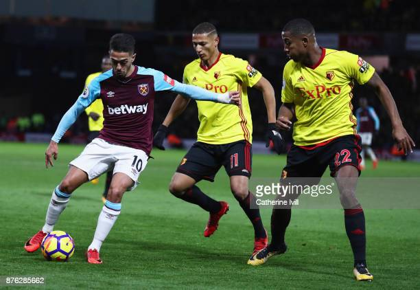 Manuel Lanzini of West Ham United is watched by Richarlison de Andrade and Marvin Zeegelaar of Watford during the Premier League match between...