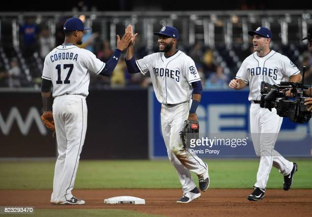 Manuel Margot of the San Diego Padres center high fives Allen Cordoba left as Matt Szczur looks on after beating the New York Mets 63 in a baseball...