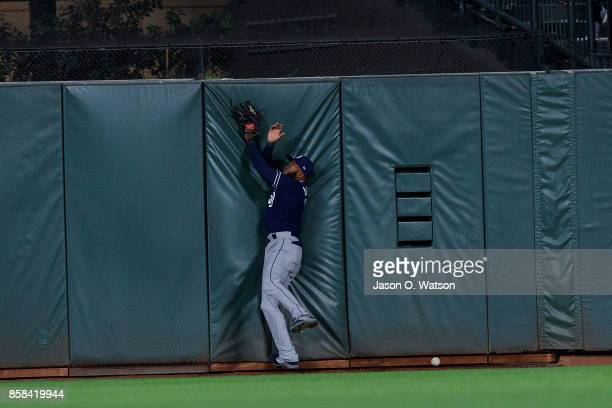 Manuel Margot of the San Diego Padres crashes into the outfield wall pursuing a fly ball hit for a triple by Hunter Pence of the San Francisco Giants...