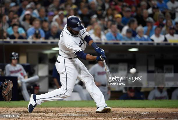 Manuel Margot of the San Diego Padres hits a sacrifice fly ball during the sixth inning of a baseball game against the Minnesota Twins at PETCO Park...