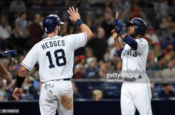 Manuel Margot of the San Diego Padres is congratulated by Austin Hedges after scoring during the sixth inning of a baseball game against the...