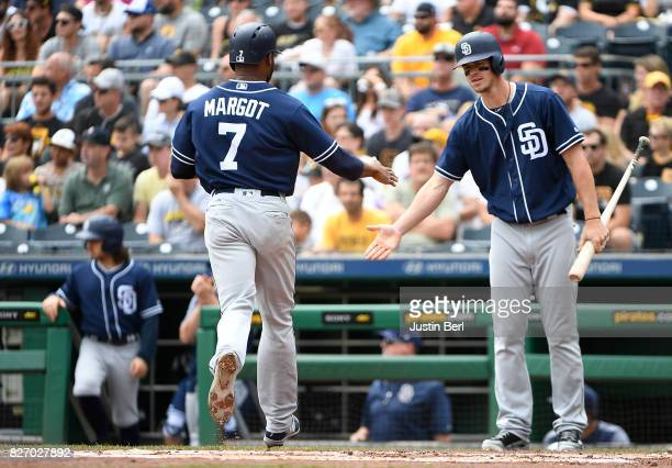 Manuel Margot of the San Diego Padres is met by Wil Myers after coming around to score on a RBI single by Cory Spangenberg in the first inning during...