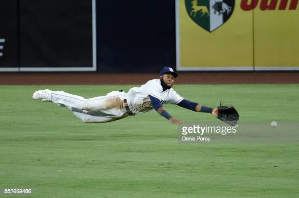 Manuel Margot of the San Diego Padres makes a diving stop on a single hit by DJ LeMahieu of the Colorado Rockies during the sixth inning of a...