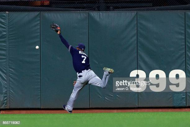 Manuel Margot of the San Diego Padres reaches for but is unable to field a fly ball hit for an RBI double by Buster Posey of the San Francisco Giants...