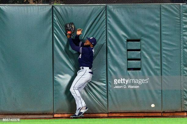 Manuel Margot of the San Diego Padres runs into the outfield wall after pursuing a fly ball hit for a triple by Hunter Pence of the San Francisco...