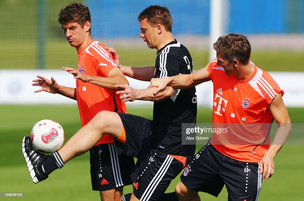 Manuel Neuer (C) is challenged by Thomas Mueller (L) and Bastian Schweinsteiger during a Bayern Muenchen training session at the ASPIRE Academy for Sports Excellence on January 6, 2013 in Doha, Qatar.