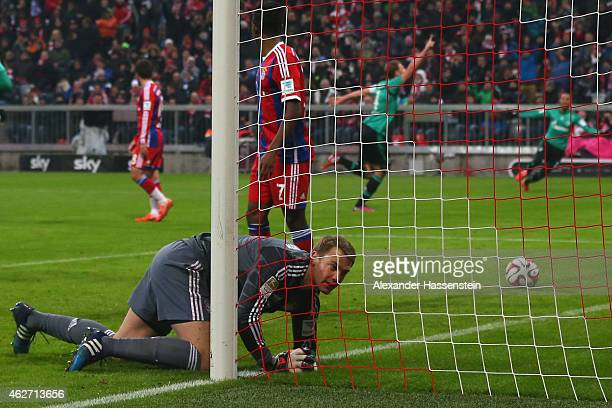 Manuel Neuer keeper of Muenchen reacts whilst Benedikt Hoewedes of Schalke celebrates the first team goal during the Bundesliga match between FC...