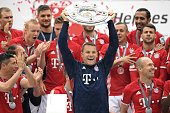 Manuel Neuer of Bayern Muenchen lifts the Meisterschale as players and staffs celebrate the Bundesliga champions after the Bundesliga match between...
