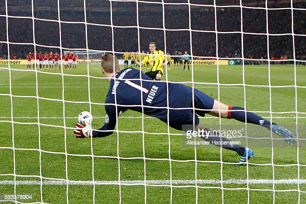 Manuel Neuer of Bayern Muenchen saves the shoot of Sven Bender of Dortmund in the penalty shootout during the DFB Cup final match between FC Bayern...